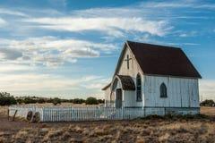 Eine alte Graslandkirche steht in einem Grasland des New Mexiko Stockfotos