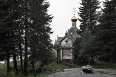 Eine alte hölzerne Kirche im Wald an der Spitze der Berge Lizenzfreies Stockbild