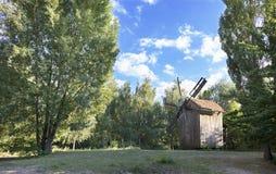 Eine alte hölzerne Windmühle im Schatten von jungen Bäumen auf einer grünen Lichtung in einem Sommerwald Lizenzfreies Stockbild