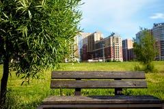 Eine alte Holzbank im Park gegen einen Hintergrund von undeutlichen Bäumen und von Gebäuden Lizenzfreie Stockbilder