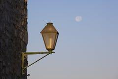 Eine alte Lampe auf einer Wand, mit einem Vollmond im Hintergrund Stockfotos