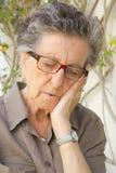 Eine alte müde Frau fällt in schlafendes Lizenzfreie Stockbilder