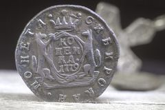 Eine alte Münze des russischen Reiches im Jahre 1779 auf dem unscharfen Hintergrund des orthodoxen Kreuzes stockfoto
