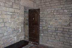 Eine alte offene Tür und eine Backsteinmauer in einem Kerker oder in einem Schloss Stockbild