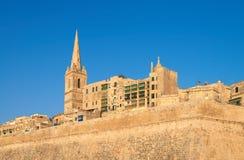 Eine alte Sandsteinkirche und -häuser in Valletta, Malta Lizenzfreie Stockbilder