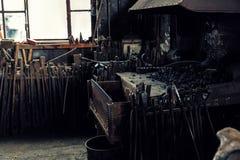 Eine alte Schmiede mit vielen Zangen und Werkzeugen in einer historischen Werkstatt f Lizenzfreies Stockbild