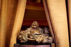 Eine alte Statuettennahaufnahme auf einer Holzoberfläche auf den Seiten des Vorhangs Talisman Hotei durch Feng Shui ist der Gott  lizenzfreies stockfoto