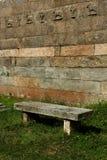 Eine alte Steinbank auf der Rasenfläche Stockbild
