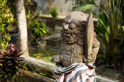 Eine alte Steingottheit mit einem Bart, einem gelockten Haar, runde Augen, große Zähne und Reißzähne, gelegen im tropischen Wald  Lizenzfreie Stockbilder