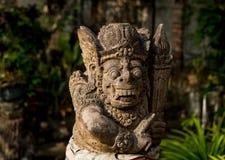 Eine alte Steingottheit mit einem Bart, einem gelockten Haar, runde Augen, große Zähne und Reißzähne, gelegen im tropischen Wald  Stockfoto