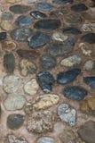 Eine alte Steinstraße von den Kopfsteinen Maurerarbeit von alten Steinen und von Ziegelsteinen Schöner Hintergrund Lizenzfreie Stockbilder