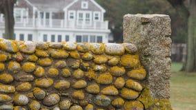 Eine alte Steinwand auf einem historischen Eigentum mit Haus in der Hintergrundgelb-Moosbedeckung Stockbild