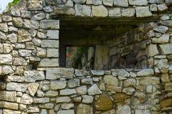 eine alte Steinwand mit einem Fenster Stockfotos