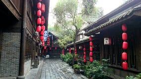 Eine alte Straße mit roten chinesischen Laternen nach mildem Regen Lizenzfreies Stockbild