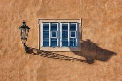 Eine alte Straßenlaterne und ein Schatten auf einer Wand mit einem Fenster Stockfotos