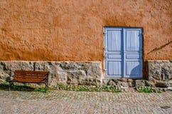 Eine alte strukturierte Wand mit einem Steinkeller, einer blauen Tür und einer Bank Stockbild