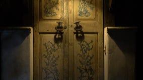 Eine alte Tür mit großen Griffen und a in einer Weinleseart stock video footage