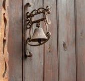 Eine alte Türklingel auf hölzernem Hintergrund Stockfotografie
