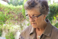 Eine alte traurige Frau, die unten schaut Lizenzfreie Stockfotografie