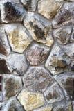 Eine alte Wand von Steinen von verschiedenen geometrischen Formen grauer, gelber und brauner Farbeals-Beschaffenheit Lizenzfreies Stockbild