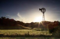 Eine alte Windmühle auf einem Gebiet bei Sonnenuntergang Lizenzfreie Stockfotografie