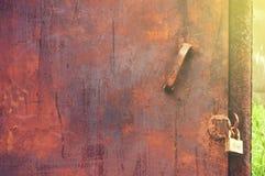 Eine altes Metallschmutzige rostige Tür mit einem Vorhängeschloß entziehen Sie Hintergrund stockfotografie