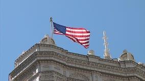 Eine amerikanische Flagge fliegt stolz gegen den blauen Sommer-Himmel stock footage