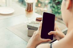 Eine Anmerkung des Frauengebrauchs-Handys kurz und Arbeiten in der Kaffeestube lizenzfreies stockfoto