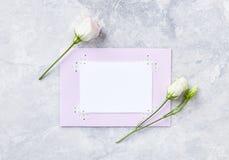 Eine Anordnung für Blumen und Grußkarte auf grauem Steinhintergrund lizenzfreie stockfotografie