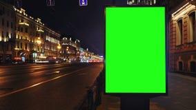 Eine Anschlagtafel mit einem grünen Schirm auf einer beschäftigten Nachtstraße stock video footage