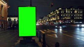 Eine Anschlagtafel mit einem grünen Schirm auf einer beschäftigten Nachtstraße stock video