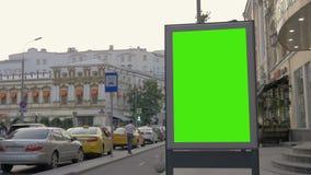 Eine Anschlagtafel mit einem grünen Schirm auf einer verkehrsreichen Straße stock footage