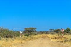 Eine Ansicht der afrikanischen Savanne und der Verkehrsschilder stockbilder