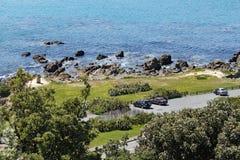 Eine Ansicht der Felsen und der Moai-Statue auf der Bank von Lyal Bay, Wellington, Neuseeland lizenzfreie stockbilder