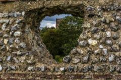 Eine Ansicht der Kathedrale durch ein Loch in Roman Wall in St Albans, Großbritannien in der Sommerzeit Lizenzfreie Stockfotografie