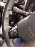 Eine Ansicht des Inneres eines Innenaufmachungsteils des Autos des Lenkrads und der befestigten Kontrollen Stockfotografie