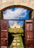 Eine Ansicht durch das Eingangstor von Kirche und von Kloster Panagia Kanakaria auf das Türkischen besetzte Seite von Zypern Stockbilder