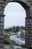 Eine Ansicht durch den Bogen des berühmten alten römischen Aquädukts von Segovia zur Stadt und zu den Straßen Lizenzfreie Stockbilder
