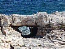 Eine Ansicht durch ein ausgezeichnetes Steinfenster auf dem blauen Meer Stockbild