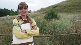 Eine Ansicht einer jungen Frau, tragendes ethnisches Kostüm, stehend auf einem Gebiet mit den gekreuzten Händen stock footage