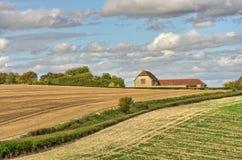 Eine Ansicht einer umgewandelten Scheune und des Ackerlands im Spätsommer stockfotos