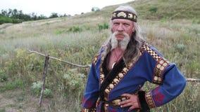 Eine Ansicht eines alten müden Mannes im ethnischen Kostüm und mit dem herrlichen Schnurrbart steht, halten Hand auf seiner Taill stock video