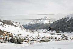 Eine Ansicht eines erstaunlichen schönen Dorfs in der Schnee umfassten Landschaft und die Berge und eine Drahtseilbahn/ein Aufzug Lizenzfreie Stockfotografie