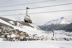 Eine Ansicht eines erstaunlichen schönen Dorfs in der Schnee umfassten Landschaft und die Berge und eine Drahtseilbahn/ein Aufzug Stockfotografie