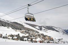 Eine Ansicht eines erstaunlichen schönen Dorfs in der Schnee umfassten Landschaft und die Berge und eine Drahtseilbahn/ein Aufzug Stockfoto