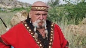 Eine Ansicht eines Mannes im ethnischen Kostüm mit Perlen im Schnurrbart, der die Trommel spielt stock video footage