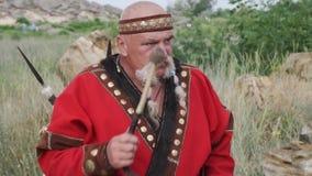 Eine Ansicht eines Mannes im ethnischen Kostüm mit Perlen im Schnurrbart, der die Trommel spielt Scythian-Kultur stock footage