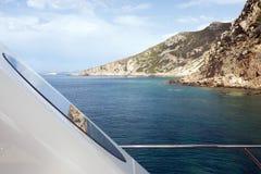 Eine Ansicht eines Meerblicks und felsige Landschaft von der Plattform eines Motorboots und eine Reflexion auf dem Fenster des Bo Lizenzfreie Stockbilder
