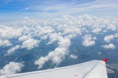Eine Ansicht obwohl ein Flugzeugfenster, wo man den Flügel und den schönen bewölkten Himmel sehen kann Lizenzfreie Stockfotografie