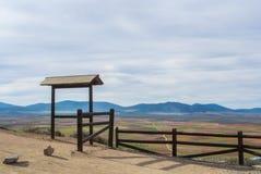 Eine Ansicht vom Beobachtungsschreibtisch mit Zaun zu den Feldern, zu den Bauernhöfen und zu den Bergen nahe Consuegra-Stadt Stockfotografie